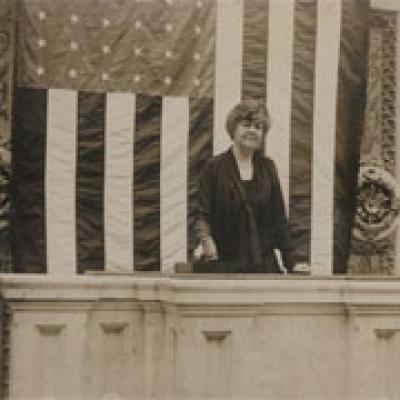 Black and white image of a Congresswoman standing in front of U.S. flag