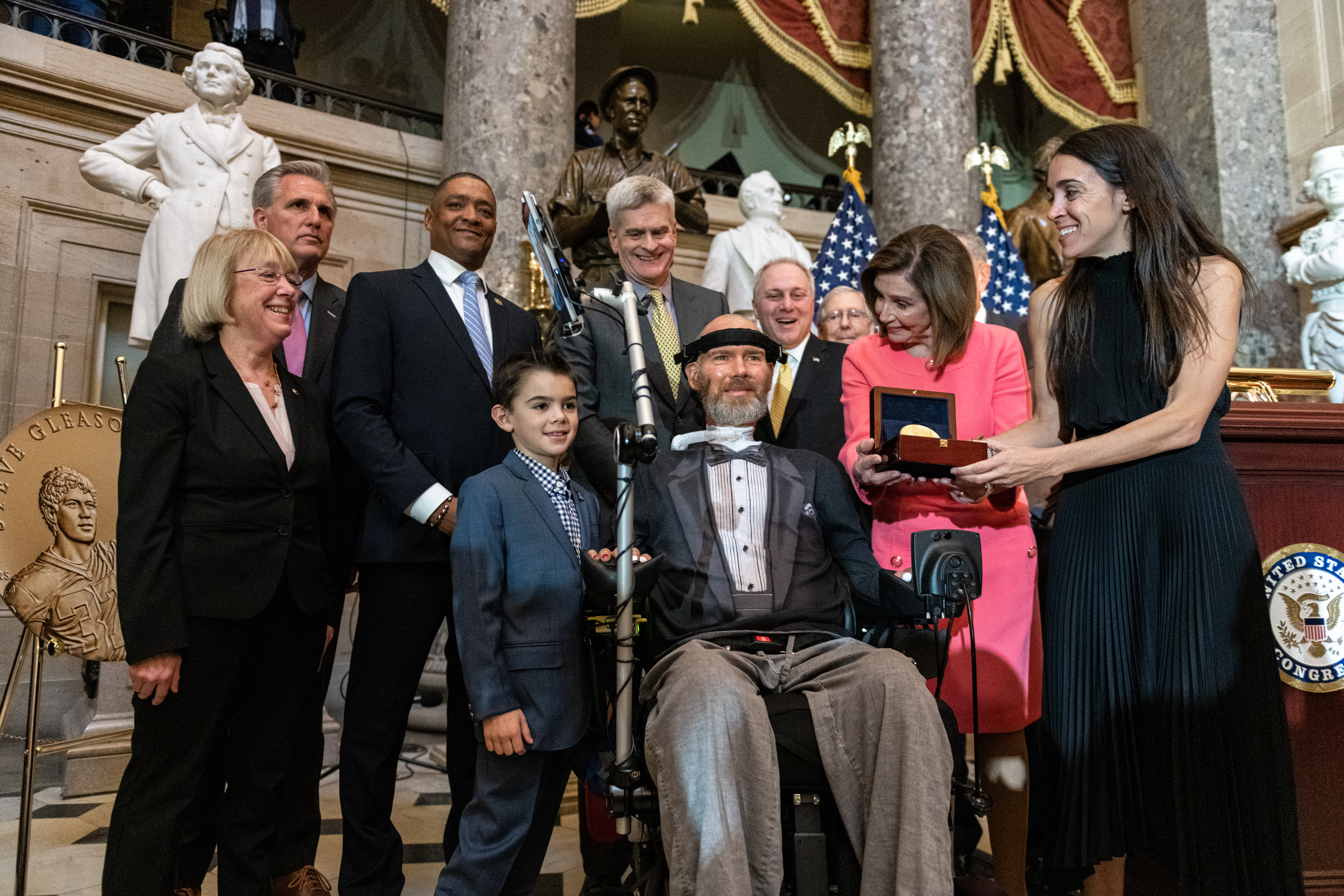 Steve Gleason, members of Congress, and the Gleason family gather around Steve.