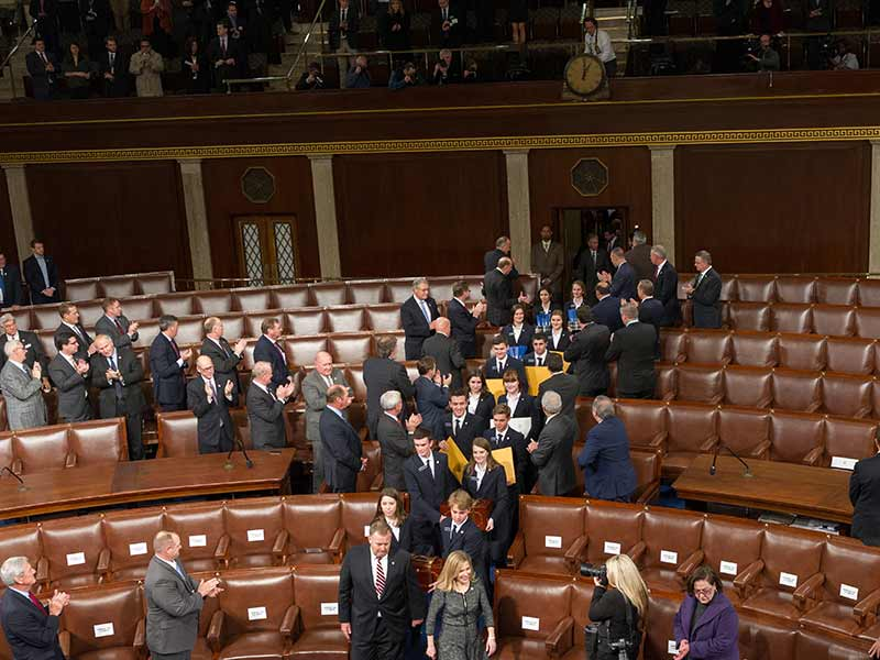 Members of the U.S. Senate standing together in the House Chamber