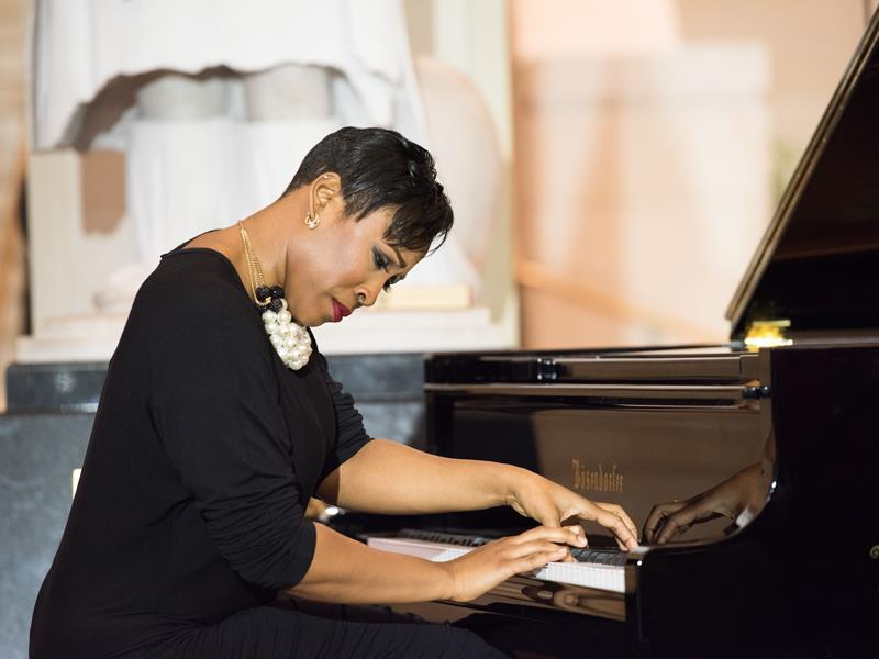 Ms. Dana Kristina-Joi Morgan playing on the piano