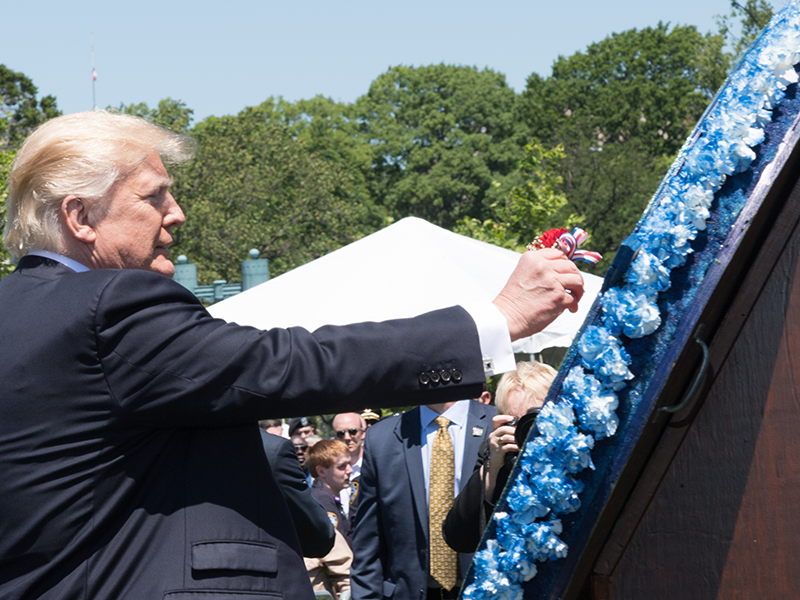 President Trump places a ribbon as a tribute to remember those officers killed in the line of duty